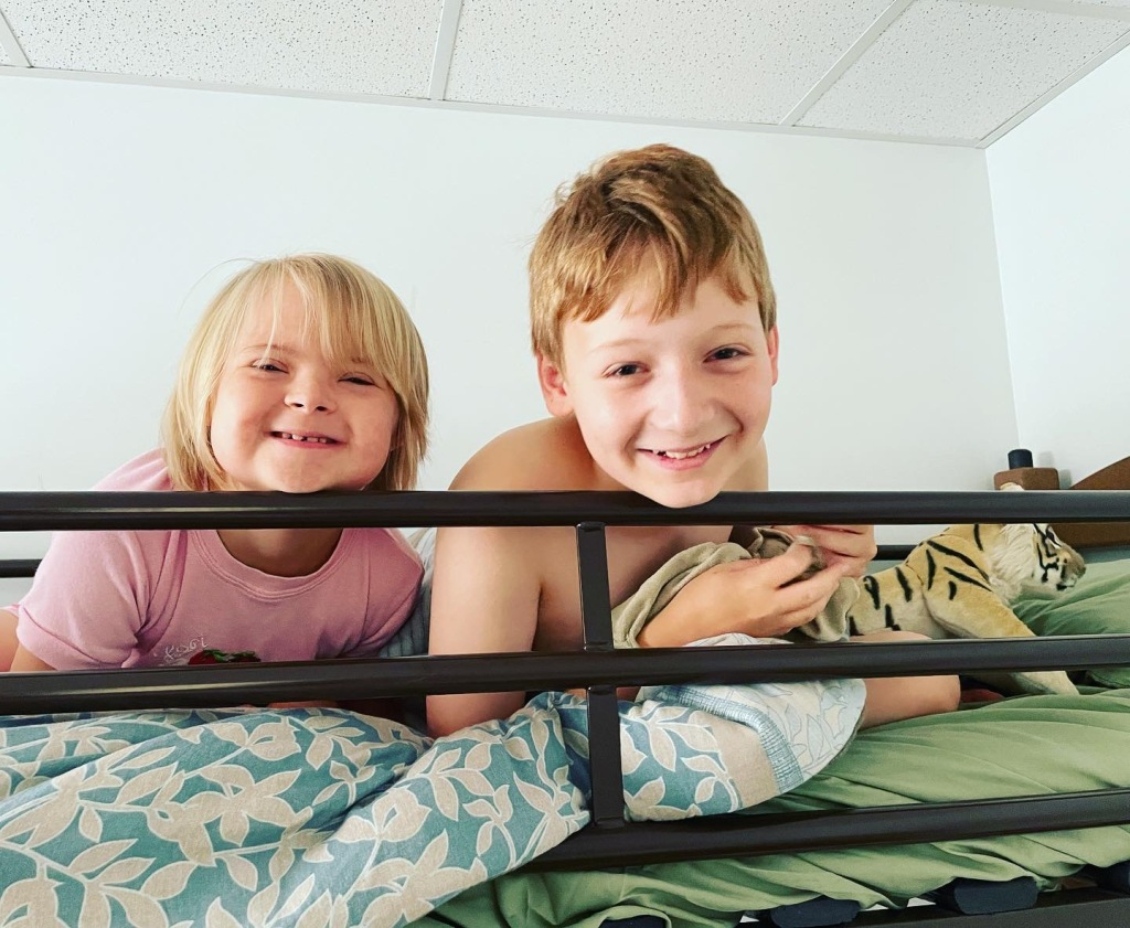 Two white children with sleepy eyes look over the railing of a top bunk bed, smiling with genuine delight. The young girl on the left has chin-length blonde hair and bangs and is wearing a pink PJ shirt. She has Down syndrome. The slightly older boy on the right has medium-short, red-brown hair and bare shoulders. A stuffed tiger is on the bed next to him.